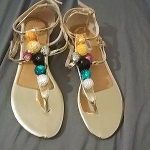 Goldtone thong sandals w/pom poms. Sze 9